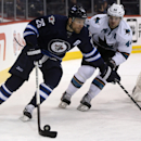 Winnipeg Jets' Blake Wheeler (26) skates ahead of San Jose Sharks' Marc-Edouard Vlasic (44) behind the net during the second period of an NHL hockey game Monday, Jan. 5, 2015, in Winnipeg, Manitoba The Associated Press