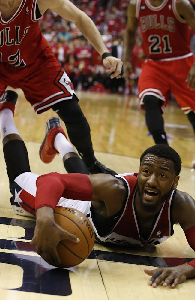 Washington Wizards guard John Wall calls a timeout as he falls to the court with the ball in the second half of Game 3 of an opening-round NBA basketball playoff series against the Chicago Bulls, Friday, April 25, 2014, in Washington. The Bulls won 100-97