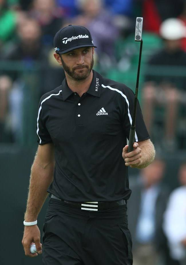 Dustin Johnson of the US acknowledges the crowd after holing his putt on the 1st green during the third day of the British Open Golf championship at the Royal Liverpool golf club, Hoylake, England, Saturday July 19, 2014