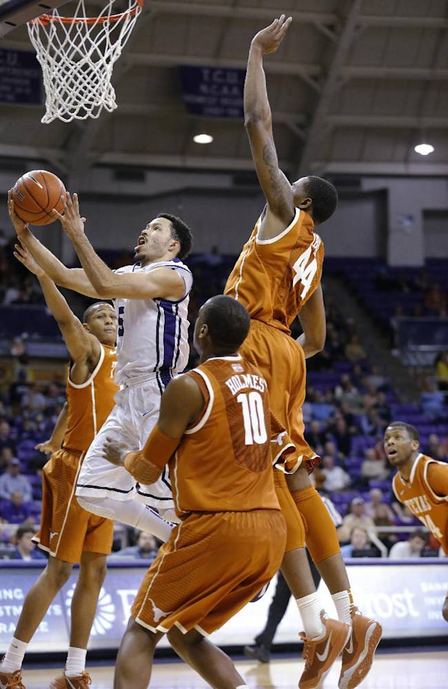 Texas guard Demarcus Holland (2), forward Jonathan Holmes (10) and center Prince Ibeh (44) defend on a shot by TCU guard Kyan Anderson (5) during the second half of an NCAA college basketball game Tuesday, Feb. 4, 2014, in Fort Worth, Texas. Texas beat TCU 59-54