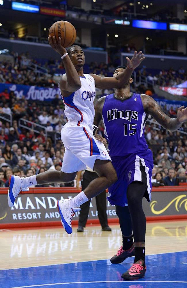 Los Angeles Clippers point guard Chris Paul, left, puts up a shot as Sacramento Kings center DeMarcus Cousins defends during the first half of their NBA basketball game, Friday, Oct. 25, 2013, in Los Angeles