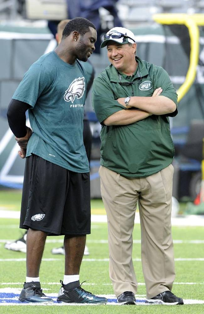 In this Aug. 29, 2013, file photo, then-Philadelphia Eagles quarterback Michael Vick, left, talks to New York Jets offensive coordinator Marty Mornhinweg before a preseason NFL football game in East Rutherford, N.J. Whether it's the second-year quarterback Geno Smith's job to lose, Mornhinweg will see what effect Vick has in what's expected to be a hotly contested competition this summer. Vick is extremely familiar with Mornhinweg's system, theoretically giving the Jets two starting-caliber quarterbacks who can run the offense with little drop-off in case of injury or ineffectiveness
