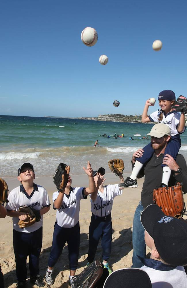 Ten-year-old Taylor Angelis, top right, sits on the shoulders of the Los Angeles Dodgers' Chris Withrow as little league players toss ball into the air at Bondi Beach in Sydney, Wednesday, March 19, 2014. The Major League Baseball season-opening two-game series between the Los Angeles Dodgers and Arizona Diamondbacks in Sydney will be played this weekend