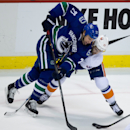 Vancouver Canucks' Shawn Matthias, left, is tied up by New York Islanders' Brian Strait during second period NHL hockey action in Vancouver, British Columbia, on Monday March 10, 2014 The Associated Press