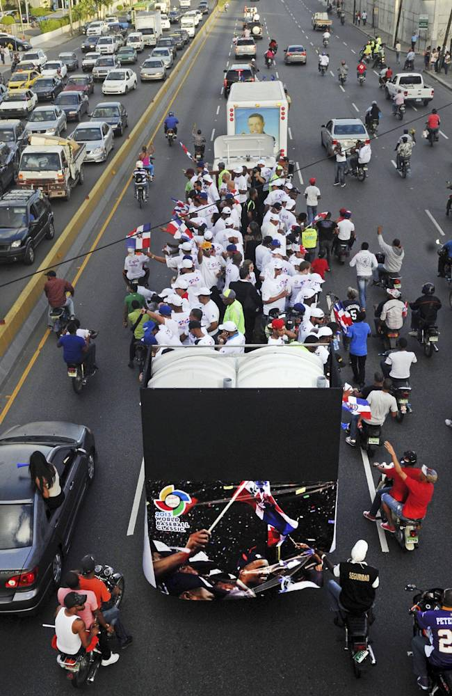 Dominican Republic baseball players ride atop a bus during the 2013 World Baseball Classic victory celebration in Santo Domingo, Dominican Republic, Thursday, Nov. 28, 2013. The Dominican Republic team won the third edition of the World Baseball Classic in March, finishing unbeaten in eight games