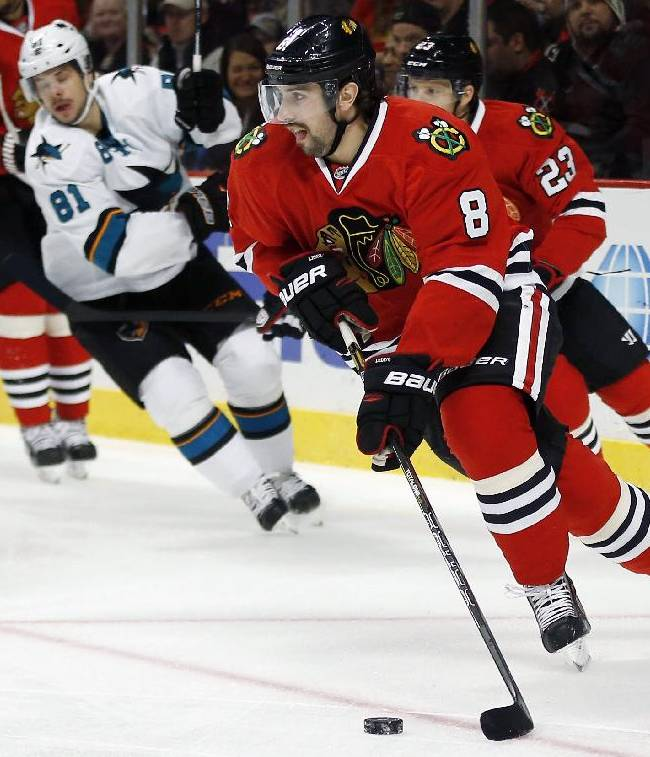 Chicago Blackhawks defenseman Nick Leddy (8) takes control of the puck from the San Jose Sharks during the first period of an NHL hockey game on Sunday, Nov. 17, 2013, in Chicago