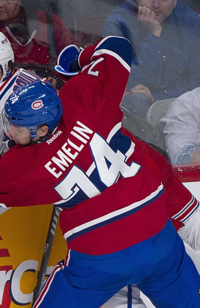 Montreal Canadiens' Alexei Emelin (74) checks New York Rangers' Benoit Pouliot into the boards during the first period of an NHL hockey game Saturday, Nov. 16, 2013, in Montreal