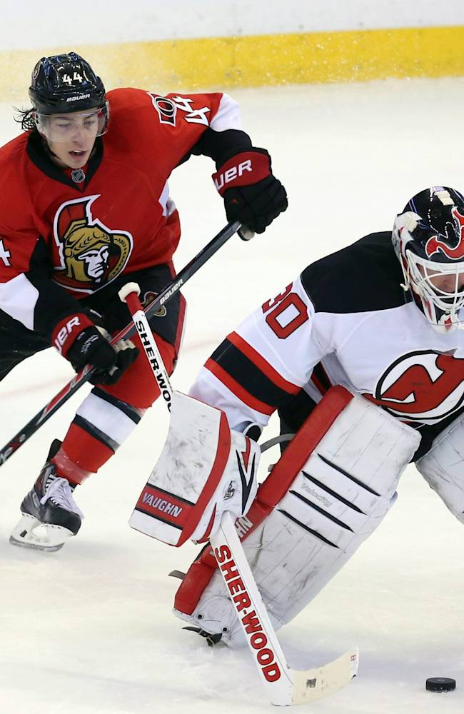New Jersey Devils goaltender Martin Brodeur, right, comes out of his goal crease to block the puck as Ottawa Senators' Jean-Gabriel Pageau gives chase during the third period of an NHL hockey game Thursday, Oct. 17, 2013, in Ottawa, Ontario. The Senators won 5-2