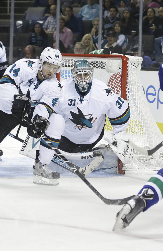 San Jose Sharks' Marc-Edouard Vlasic (44) blocks a shot attempt from Vancouver Canucks' Dan Hamhuis (2) during the second period of a preseason NHL hockey game on Tuesday, Sept. 24, 2013, in San Jose, Calif