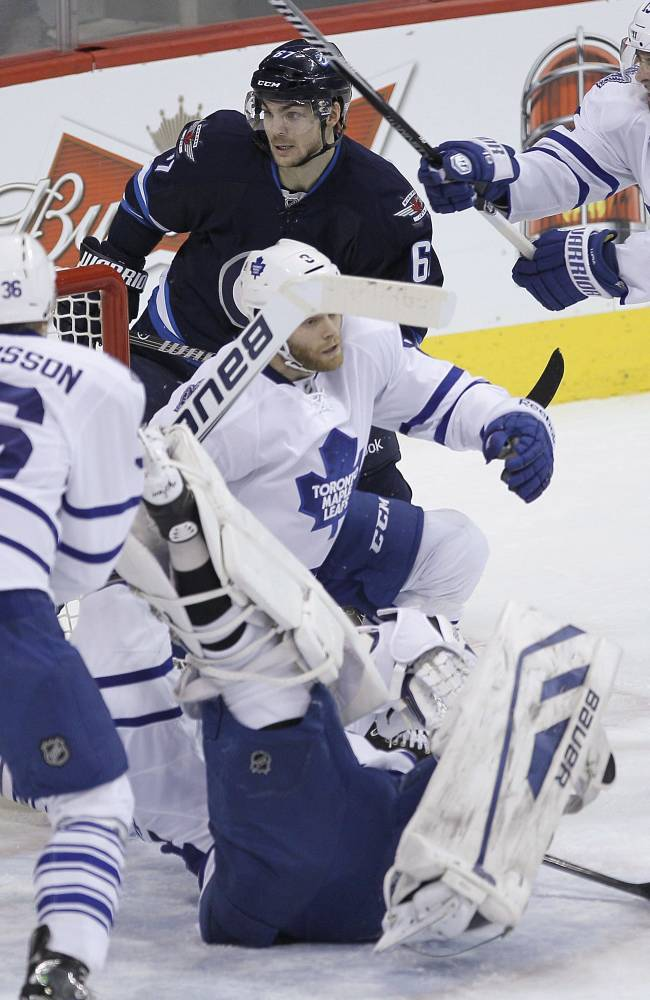 Winnipeg Jets' Michael Frolik (67) looks for the rebound off Toronto Maple Leafs goaltender James Reimer (34) as Maple Leafs' Carl Gunnarsson (36) and Joffrey Lupul (19) defend during the first period of an NHL hockey game Saturday, Jan. 25, 2014, in Winnipeg, Manitoba
