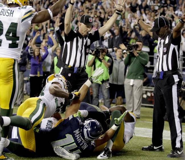 In this Sept. 24, 2012, file photo, an official, rear center, signals for a touchdown by Seattle Seahawks wide receiver Golden Tate, obscured, as another official, at right, signals a touchback, on the controversial last play of an NFL football game against the Green Bay Packers in Seattle. It's been nearly two full years since the Packers and Seahawks met in the regular season, a game that forever became known as the
