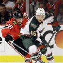 Chicago Blackhawks' Marcus Kruger (16) battles for the puck against Minnesota Wild's Jared Spurgeon (46) during the second pe