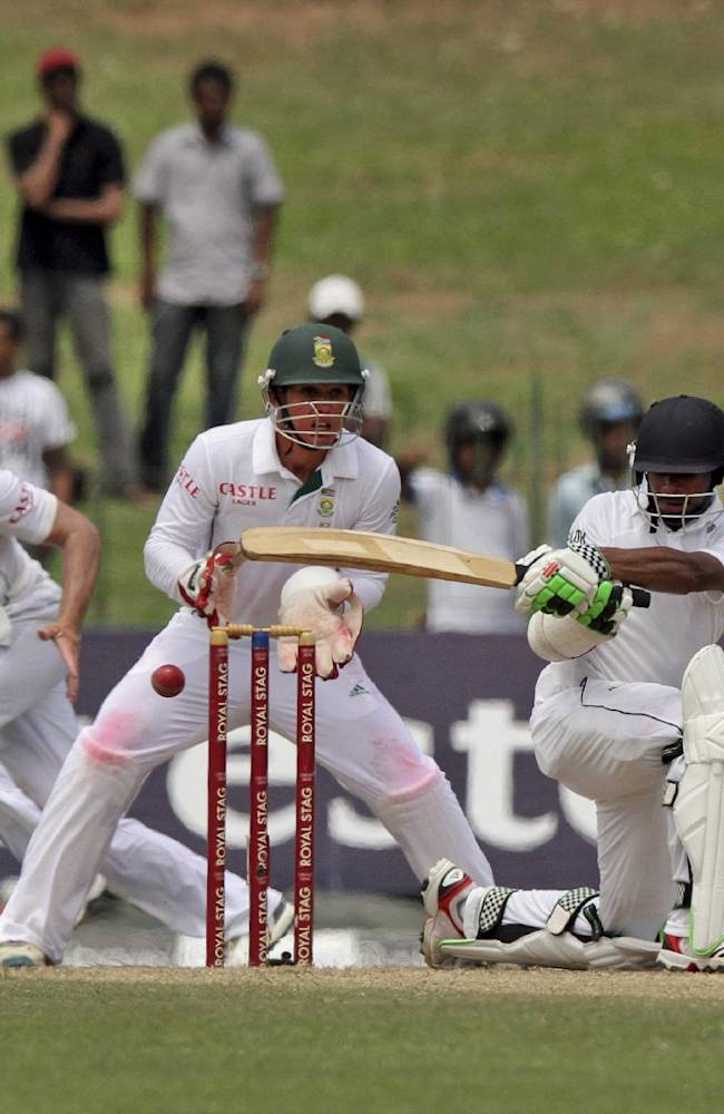 Sri Lanka's Niroshan Dickwella plays a shot as South Africa's wicket keeper Quinton de Kock, centre, and AB de Villiers watch on the second day of the second cricket test match between them in Colombo, Sri Lanka, Friday, July 25, 2014