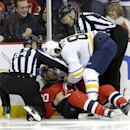 Buffalo Sabres left wing Marcus Foligno center right, holds up the head of New Jersey Devils center Ryan Carter, center left, after Foligno punched Carter during a fight as linesman Tony Sericolo (84) and linesman Tim Nowak (77) check on them during the f