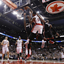Toronto Raptors' DeMar DeRozan (10) goes up to shoot against Miami Heat's Chris Bosh (1) and Dwyane Wade (3) during the second half of an NBA basketball game in Toronto, Friday, Nov. 29, 2013 The Associated Press