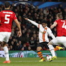 Donetsk's Douglas Costa, centre takes a shot on goal during their Champions League group A soccer match between Manchester United and Shakhtar Donetsk at Old Trafford Stadium, Manchester, England, Tuesday, Dec. 10, 2013