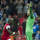 CAPTION CORRECTION, CORRECTS ID OF GOALKEEPER - Arsenal's Lukasz Fabianski, right, and Bacary Sagna, left, celebrate after winning against Wigan Athletic, during their English FA Cup semifinal soccer match, at the Wembley Stadium in London, Saturday, Apri