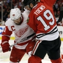 Detroit Red Wings' Henrik Zetterberg (40) battles for the puck against Chicago Blackhawks' Jonathan Toews (19) during the fir