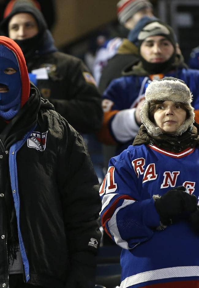 Fans are dressed for frigid temperatures during the first period of an outdoor NHL hockey game between the New York Islanders and the New York Rangers at Yankee Stadium in New York, Wednesday, Jan. 29, 2014