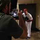 David Wallace, staff photographer for the Arizona Republic newspaper, left, checks the back of his camera as he shoots a portrait of Arizona Diamondbacks pitcher J.J. Putz, right, during the team's photo day before a spring training baseball workout, Wedn