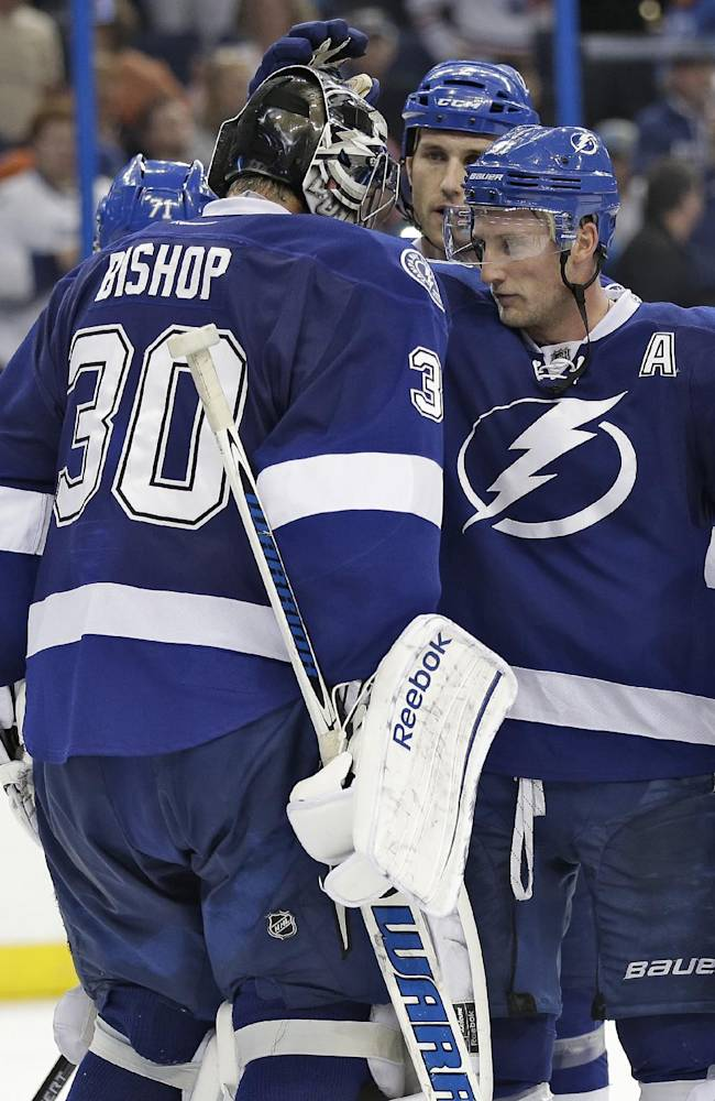 Tampa Bay Lightning center Steven Stamkos, right, celebrates with goalie Ben Bishop after the team defeated the Edmonton Oilers 4-2 during an NHL hockey game Thursday, Nov. 7, 2013, in Tampa, Fla