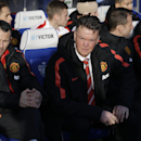 Manchester United's manager Louis van Gaal, second left, and coach Ryan Giggs, left, wait for the start of the English Premier League soccer match between QPR and Manchester United at Loftus Road stadium in London, Saturday, Jan. 17, 2015