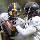 Pittsburgh Steelers running back LeGarrette Blount, right, tries to strip the ball from fellow Steelers running back Le'Veon Bell in a drill during a combined NFL football training camp session with the Buffalo Bills in Latrobe, Pa. on Wednesday, Aug. 13, 2014. (AP Photo/Keith Srakocic)