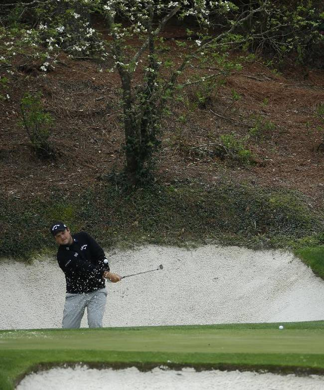 Patrick Reed chips out of a bunker on the 12th hole during a practice round for the Masters golf tournament Tuesday, April 8, 2014, in Augusta, Ga