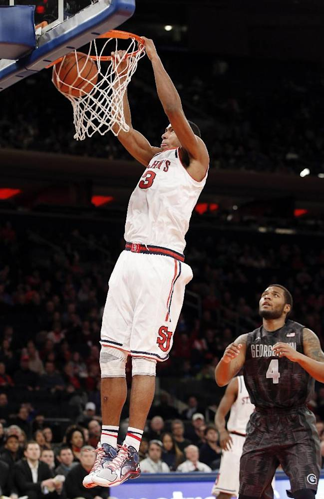 St. John's forward Orlando Sanchez, left, dunks as Georgetown guard D'Vauntes Smith-Rivera (4) stands near from the floor during the second half of an NCAA college basketball game at Madison Square Garden in New York, Sunday, Feb. 16, 2014.  St. John's won 82-60