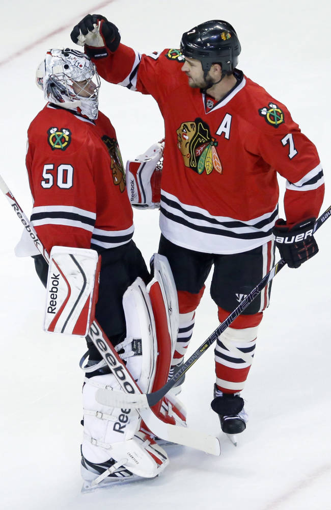Chicago Blackhawks goalie Corey Crawford (50) and defenseman Brent Seabrook celebrate the Blackhawks' 2-0 win over the Detroit Red Wings after an NHL preseason hockey game Tuesday, Sept. 17, 2013, in Chicago