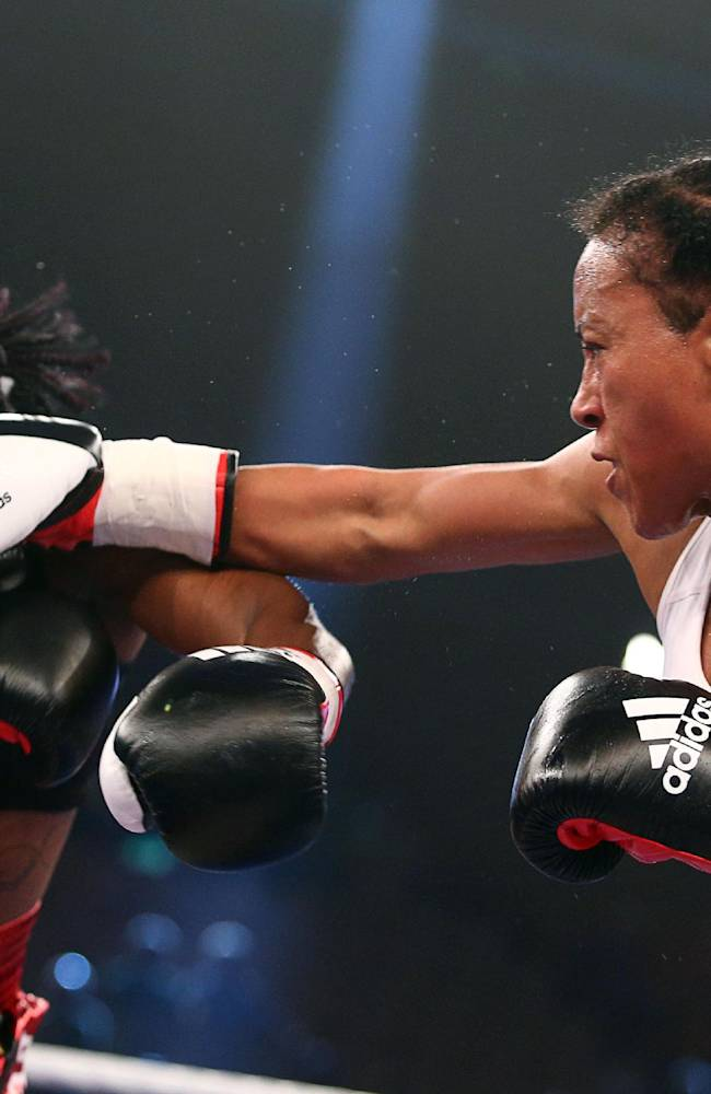 In this picture taken Saturday June 7, 2014, Colombian-born Norwegian ,Cecilia Braekhus,  right, lands a punch on Nigerian-born German challenger  Jessica Balogun, left, during their  women's welterweight  boxing  title bout in Schwerin, eastern Germany. Braekhus won the boxing fight