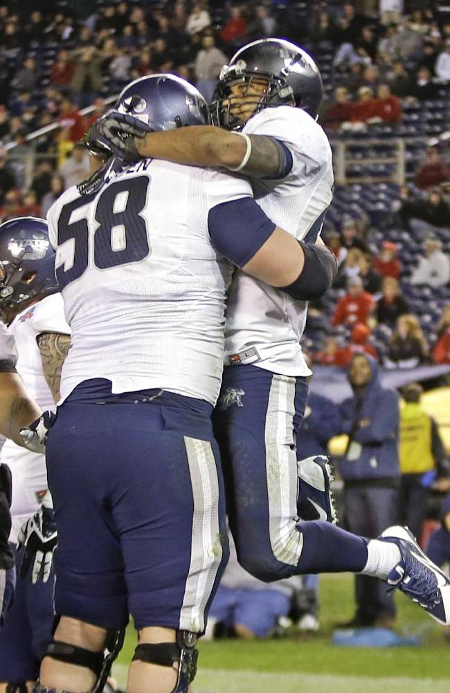 Utah State's Joey DeMartino is lifted by Tyler Larsen after his one yard touchdown run in Utah State's 21-14 victory over Northern Illinois in the Poinsettia Bowl NCAA college football game, Thursday, Dec. 26, 2013, in San Diego