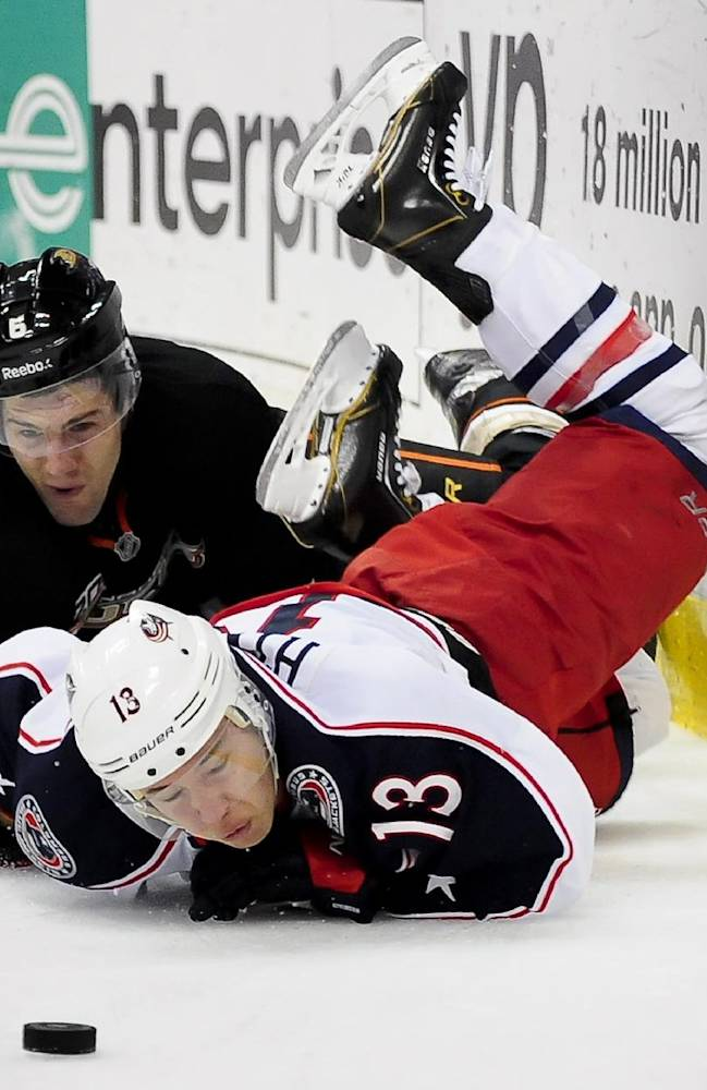 Anaheim Ducks defenseman Ben Lovejoy, left, and Columbus Blue Jackets right wing Cam Atkinson, battle for the puck during the first period of an NHL hockey game, Monday, Feb. 3, 2014, in Anaheim, Calif