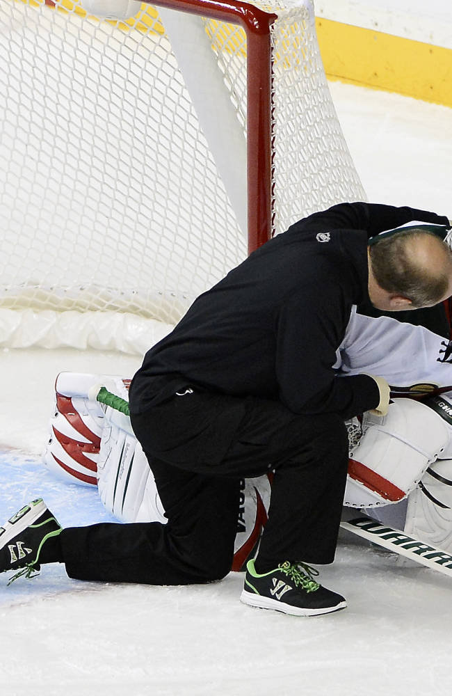 Minnesota Wild goalie Niklas Backstrom, right, of Finland, is attended to after colliding with Nashville Predators forward Eric Nystrom and was taken out of the game in the first period of an NHL hockey game on Tuesday, Oct. 8, 2013, in Nashville, Tenn