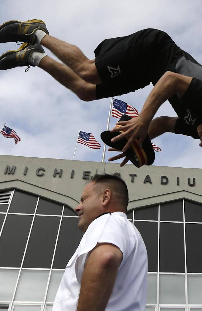 Army gymnastics team member Kip Webber of Boxborough, Mass., grabs the hat from  Col. Joseph DeAntona, deputy military athletic director, during a demonstration outside Michie Stadium before an NCAA college football game between Army and Wake Forest on Saturday, Sept. 21, 2013, in West Point, N.Y