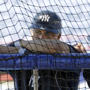 New York Yankees right fielder Carlos Beltran peers into the batting cage from behind the netting as hitting coach Kevin Long, right, talks to him before a spring training baseball game against the Toronto Blue Jays in Dunedin, Fla., Wednesday, March 26,