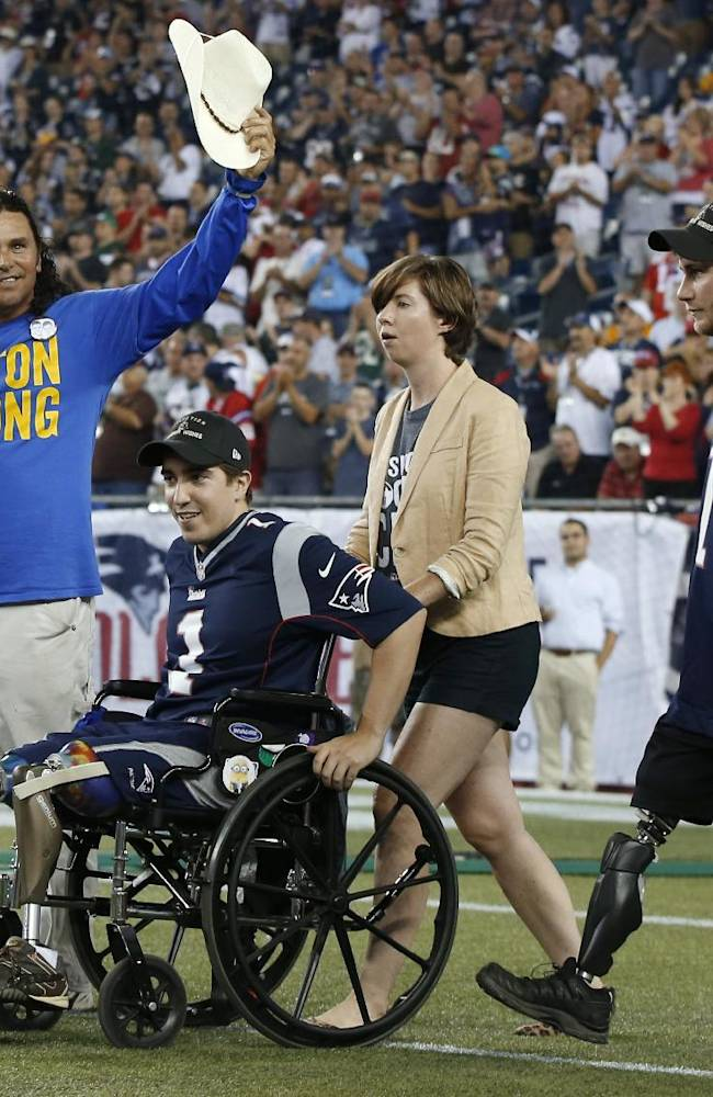 A wounded veteran, right, and Jeff Bauman, in wheelchair, who lost his legs in the Boston Marathon bombing, are honored on the field with other bombing survivors before an NFL football game Thursday, Sept. 12, 2013, in Foxborough, Mass. At left is Carlos Arredondo, who helped Bauman at the time of the blast