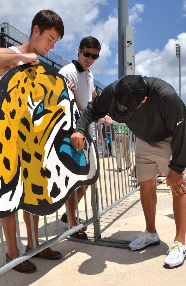 Dalton Dee, left, a student from Fleming Island, holds a large jaguar head he painted for Jacksonville Jaguars head coach Gus Bradley to sign after the NFL team's football training camp, on Friday, July 25, 2014, in Jacksonville, Fla