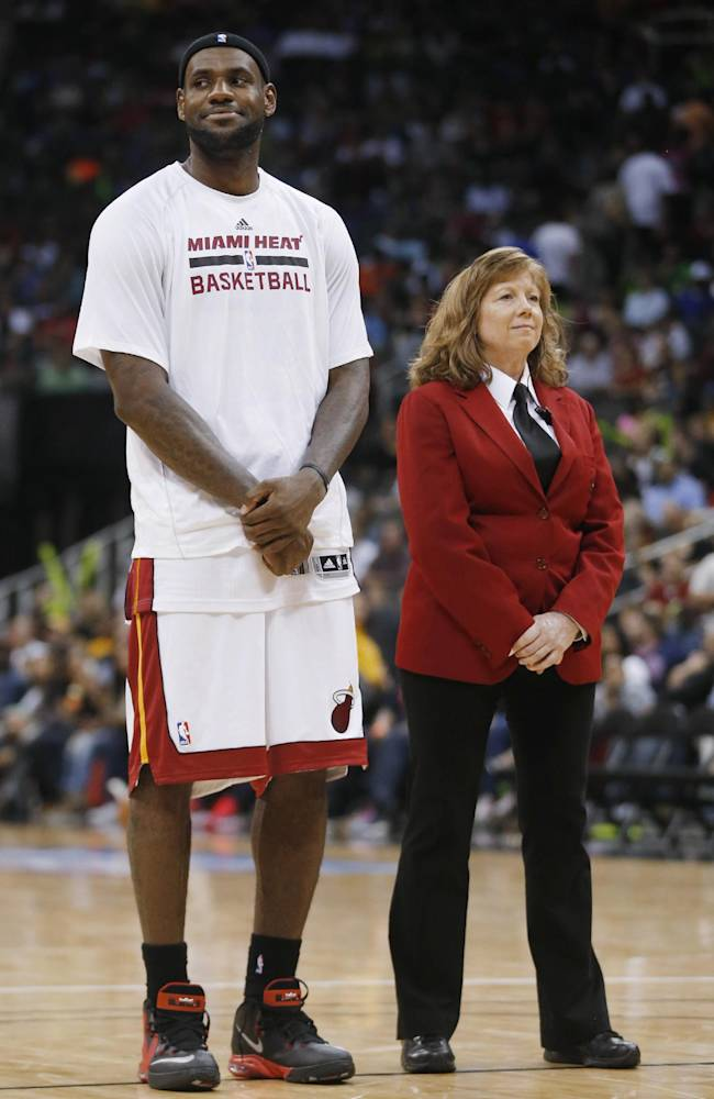 Miami Heat forward LeBron James (6) stands next to a floor security guard during a timeout in the second half of the Heat's preseason NBA basketball game against the Charlotte Bobcats in Kansas City, Mo., Friday, Oct. 11, 2013. The Heat defeated the Bobcats 86-75
