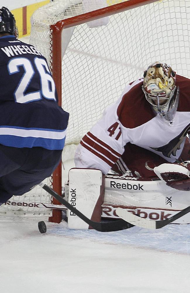 Winnipeg Jets' Blake Wheeler (26) attempts to jam the puck in the corner past Phoenix Coyotes goaltender Mike Smith (41) as Coyotes' Antoine Vermette (50) defends during first-period NHL hockey game action in Winnipeg, Manitoba, Thursday, Feb. 27, 2014. (AP Phoyo/The Canadian Press, John Woods)