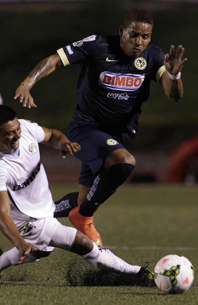 Michael Arroyo of Mexico's America, top, is tackled by Guatemala's Comunicaciones Carlos Castrillo during their Concacaf Champions League soccer match in Guatemala City Tuesday, Aug. 26, 2014