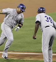 Colorado Rockies' Willin Rosario, left, is cheered on by Stu Cole while running the bases after hitting a home run in the third inning against the Philadelphia Phillies in a baseball game, Tuesday, Aug. 20, 2013, in Philadelphia. (AP Photo/Laurence Kesterson)