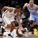 Denver Nuggets guard Randy Foye (4) runs down court leaving Brooklyn Nets forward Reggie Evans, bottom center, and Brooklyn Nets guard Joe Johnson (7) in his wake in the second half of an NBA basketball game Tuesday, Dec. 3, 2013, in New York. The Nuggets