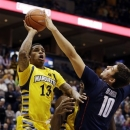 Marquette's Vander Blue (13) shoots against Connecticut's Tyler Olander (10) during the first half of an NCAA college basketball game, Tuesday, Jan. 1, 2013, in Milwaukee. (AP Photo/Jeffrey Phelps)