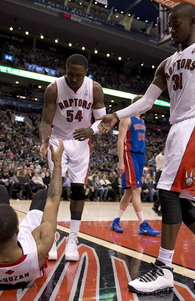 Toronto Raptors guard DeMar DeRozan. bottom, is helped up by teammates Amir Johnson (15), Patrick Patterson (54) and Terrence Ross (31) after being fouled during fourth-quarter NBA basketball game action against the Detroit Pistons in Toronto, Wednesday, Jan. 8, 2014