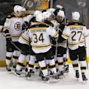Boston Bruins players swarm Ryan Spooner after he scored the game-winning goal during overtime of an NHL hockey game, Friday, Feb. 27, 2015, in Newark, N.J. The Bruins won 3-2 in overtime. (AP Photo/Julio Cortez)