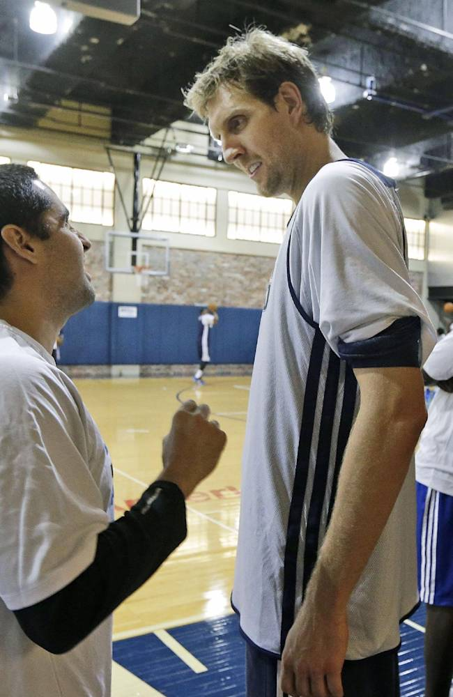 Dallas Mavericks Dirk Nowitzki (41) of Germany, right, listens to assistant coach Kaleb Canales during NBA basketball training camp Thursday, Oct. 3, 2013, in Dallas