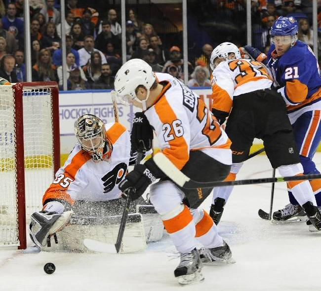 Philadelphia Flyers goalie Steve Mason (35) stretches to capture the puck as  Erik Gustafsson (26) and Mark Streit (32) defend against New York Islanders right wing Kyle Okposo (21) in the second period of an NHL hockey game at the Nassau Coliseum on Saturday, Oct. 26, 2013, in Uniondale, N.Y