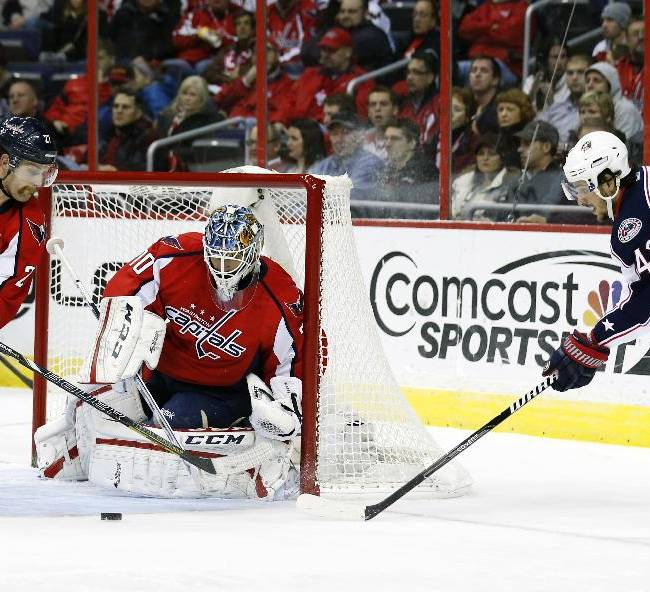 Washington Capitals defenseman Karl Alzner, left, works to clear the puck from in front of goalie Braden Holtby, center, as Columbus Blue Jackets center Artem Anisimov (42), of Russia, attacks, in the second period of an NHL hockey game Tuesday, Nov. 12, 2013, in Washington