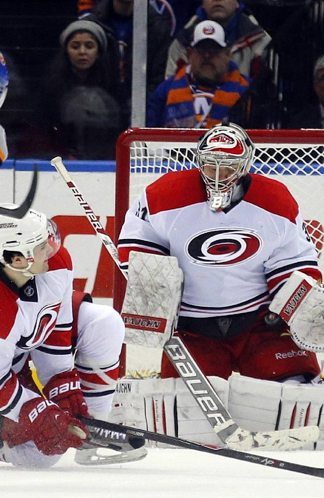 Carolina Hurricanes goalie Anton Khudobin, right, makes a save on a shot by New York Islanders left wing Thomas Vanek (26) in the third period of an NHL hockey game in Uniondale, N.Y., Saturday Jan. 4, 2014. The Hurricanes won 3-2